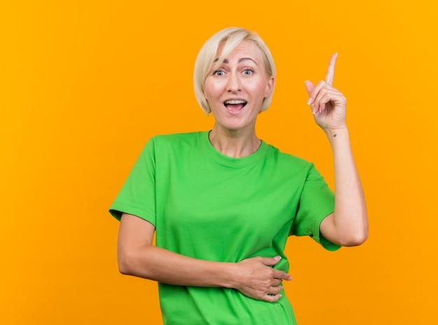 Impresionada mujer rubia de mediana edad mirando al frente apuntando hacia arriba aislado en la pared amarilla