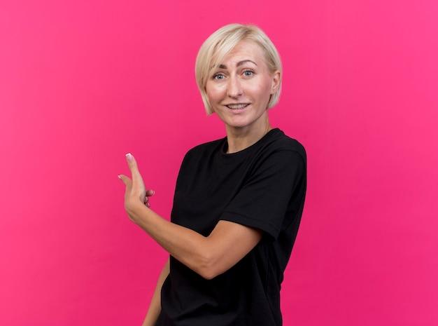 Impresionada mujer rubia de mediana edad mirando al frente apuntando detrás aislado en la pared rosa