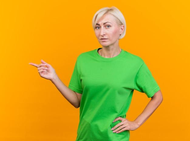 Impresionada mujer rubia de mediana edad mirando al frente manteniendo la mano en la cintura apuntando al lado aislado en la pared amarilla