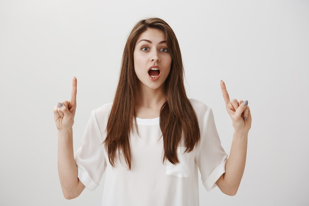 Impresionada mujer sorprendida contando grandes noticias y apuntando con el dedo hacia arriba