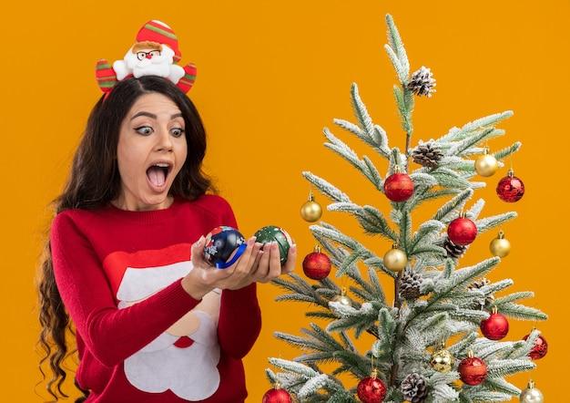 Impresionada niña bonita con diadema de santa claus y suéter de pie cerca del árbol de navidad decorado sosteniendo mirando adornos navideños aislados sobre fondo naranja
