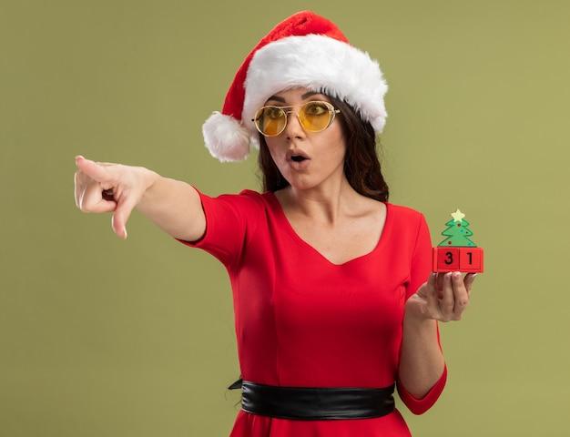 Impresionada niña bonita vistiendo gorro de papá noel y gafas sosteniendo el juguete del árbol de navidad con fecha mirando y apuntando al lado aislado sobre fondo verde oliva