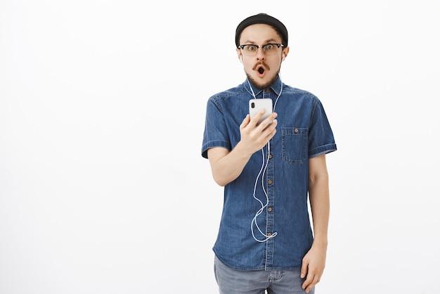 Impresionado chico guapo sin palabras con bigote en anteojos y gorro negro jadeando abriendo la boca con sonido wow mirando después de leer un mensaje impactante en un teléfono inteligente con auriculares