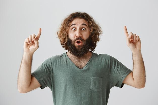 Impresionado y emocionado guapo barbudo apuntando con el dedo hacia arriba, hacer anuncio