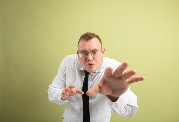 Impresionado hombre eslavo adulto con gafas y corbata mirando a la cámara estirando la mano hacia la cámara aislada sobre fondo verde oliva con espacio de copia