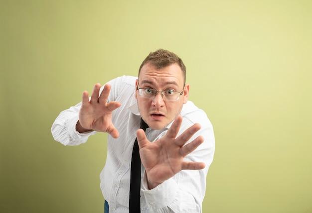 Impresionado hombre eslavo adulto con gafas y corbata mirando a la cámara estirando las manos gesticulando no aislado sobre fondo verde oliva con espacio de copia
