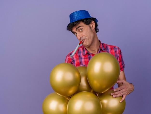 Impresionado hombre de fiesta de mediana edad con sombrero de fiesta de pie detrás de globos tocando un soplador de fiesta mirando al frente aislado en la pared púrpura con espacio de copia