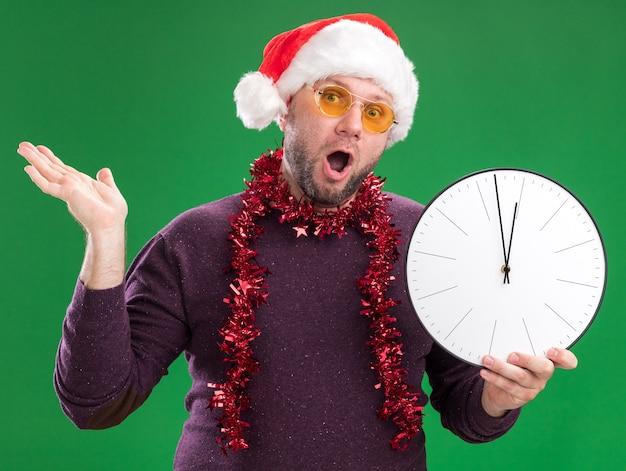 Impresionado hombre de mediana edad con gorro de papá noel y guirnalda de oropel alrededor del cuello con gafas sosteniendo el reloj que muestra la mano vacía aislada en la pared verde
