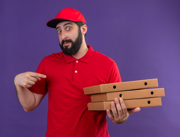 Impresionado joven apuesto repartidor caucásico vestido con uniforme rojo y gorra sosteniendo y apuntando a cajas de pizza aisladas en púrpura