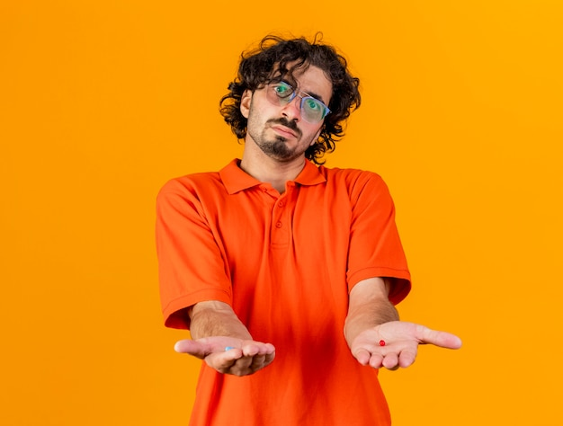 Impresionado joven enfermo caucásico con gafas mirando a la cámara estirando cápsulas médicas hacia la cámara aislada sobre fondo naranja con espacio de copia