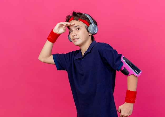 Impresionado joven guapo deportivo con diadema y muñequeras y auriculares brazalete de teléfono con aparatos dentales corriendo mirando a distancia aislada en la pared rosa con espacio de copia