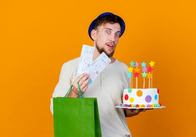 Impresionado joven guapo eslavo partido con sombrero de fiesta sosteniendo boletos de avión bolsa de papel y pastel de cumpleaños con estrellas mirando a cámara aislada sobre fondo naranja con espacio de copia