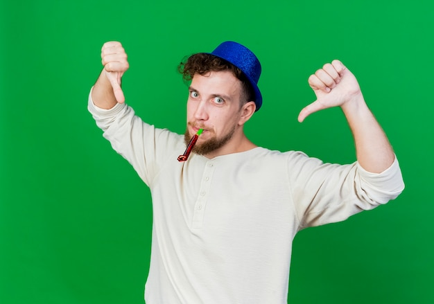 Impresionado joven guapo partido eslavo con sombrero de fiesta sosteniendo el soplador de fiesta en la boca mirando a la cámara mostrando los pulgares hacia abajo aislado sobre fondo verde