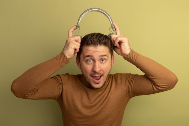 Impresionado joven guapo rubio sosteniendo auriculares por encima de la cabeza mirando al frente aislado en la pared verde oliva