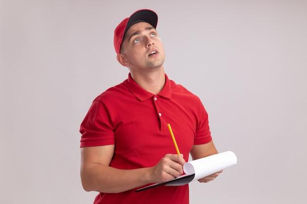 Impresionado mirando hacia arriba joven repartidor vestido con uniforme con gorra sosteniendo el portapapeles con lápiz aislado en la pared blanca