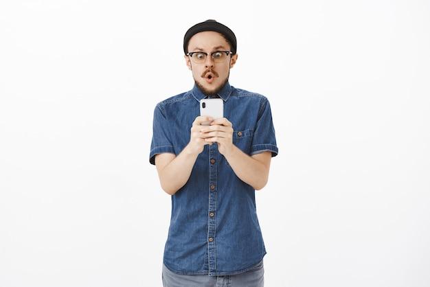 Impresionado, sin palabras, emocionado y asombrado guapo con barba con gafas y gorro sosteniendo un teléfono inteligente mirando sorprendido a la pantalla del teléfono inteligente como si estuviera viendo noticias increíbles doblando los labios con un sonido increíble