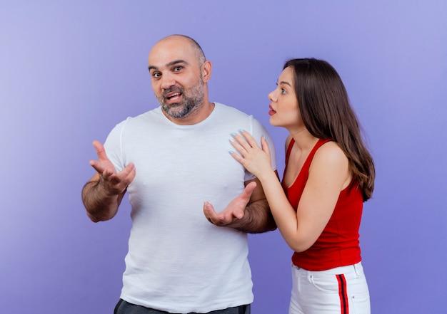 Impresionado pareja adulta hombre mirando mostrando las manos vacías y la mujer tocando su hombro mirándolo
