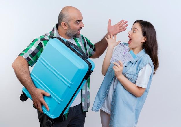 Impresionado viajero adulto pareja hombre sosteniendo maleta mujer sosteniendo boletos de viaje manteniendo la mano en el aire y mirando el uno al otro