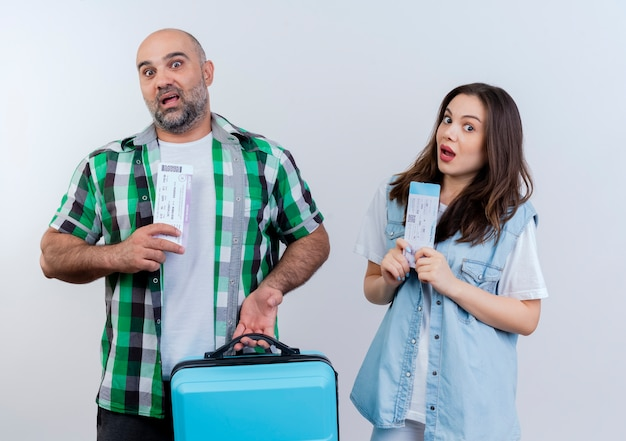 Impresionado viajero adulto pareja hombre sujetando la maleta y ambos con billetes de viaje mirando