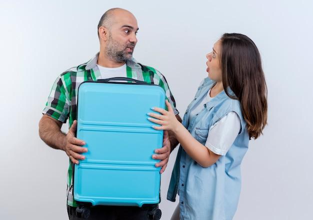 Impresionado viajero adulto pareja hombre sujetando la maleta y la mujer poniendo la mano en la maleta, ambos mirando el uno al otro