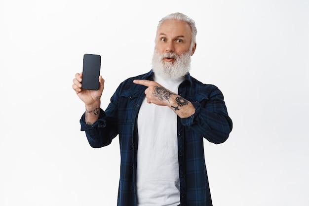 Impresionado viejo tatuado apuntando a la pantalla del teléfono inteligente, mostrando una nueva aplicación móvil increíble, muestra una aplicación, de pie sobre una pared blanca