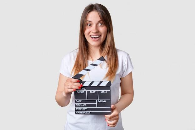 Impresionante alegre directora caucásica sostiene claqueta de cine