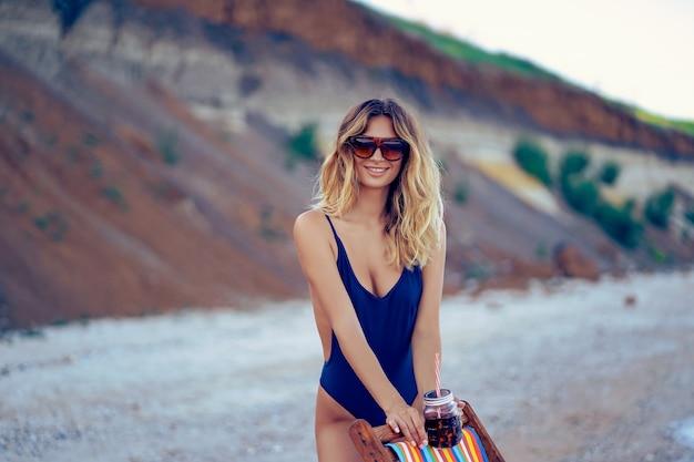 Impresionante belleza mujer rubia en gafas de sol, traje de baño relajante en la playa y bebidas cóctel