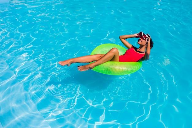Impresionante bronceada hermosa joven en bikini nadando en la piscina y relajarse en elegantes trajes de baño.