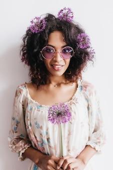 Impresionante chica africana en gafas de sol posando con allium. filmación en interiores de adorable modelo femenino rizado con flores de color púrpura.