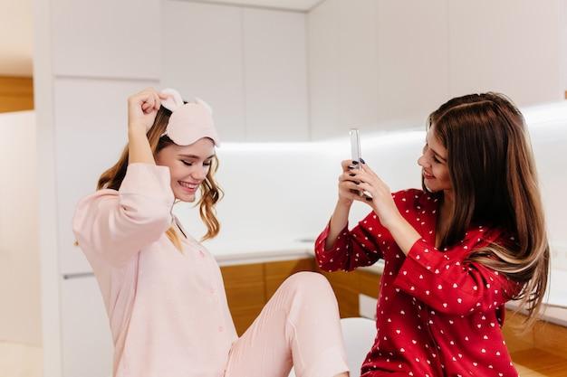 Impresionante chica en antifaz divertido posando para su hermana en la mañana. mujer joven de pelo oscuro en ropa de dormir roja sosteniendo el teléfono y haciendo fotos.