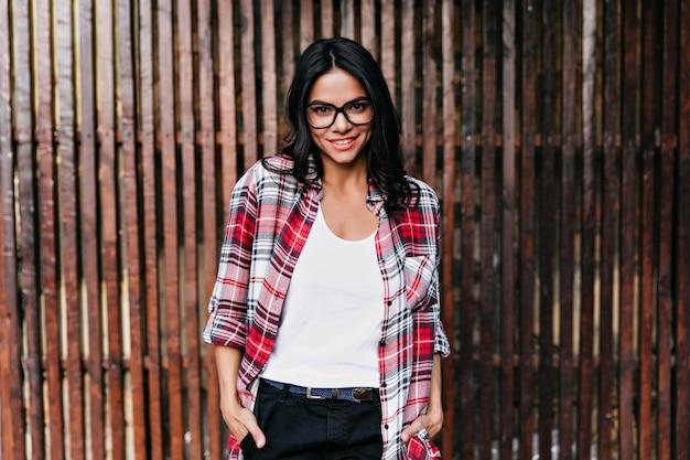 Impresionante chica con gafas de pie en pose de confianza y sonriendo. disparo al aire libre de dama latina posando con la mano en el bolsillo en la pared de madera.