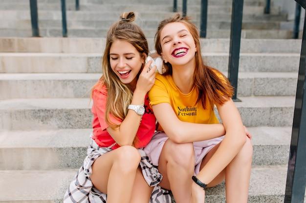 Impresionante chica de pelo largo en reloj de pulsera blanco descansando en la escalera junto a un amigo riendo en camisa amarilla