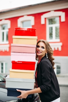 Impresionante dama con pila de cajas de zapatos.