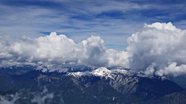 Impresionante disparo de alto ángulo de montañas nevadas bajo las nubes y el cielo de fondo