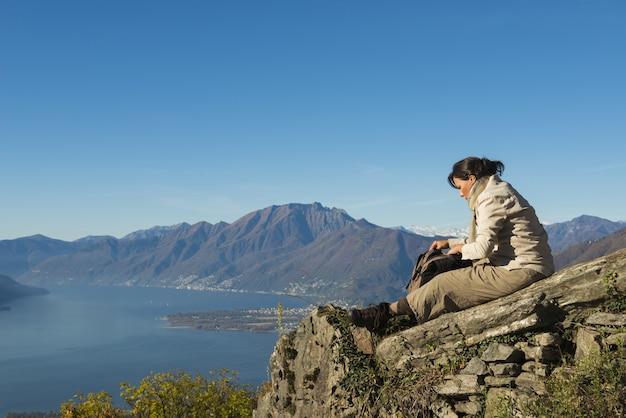 Impresionante escena de una mujer sentada en la cima de la montaña.