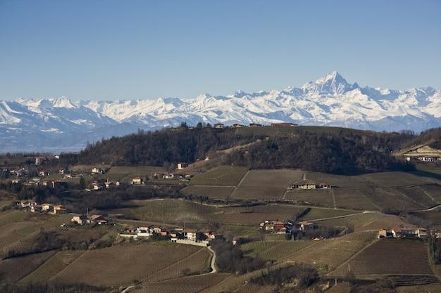 Impresionante foto de las casas con las montañas cubiertas de nieve.
