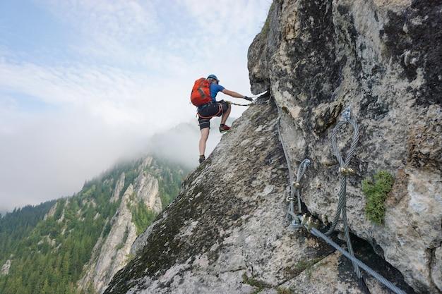 Impresionante foto de un joven trepando por un acantilado en un día frío y brumoso