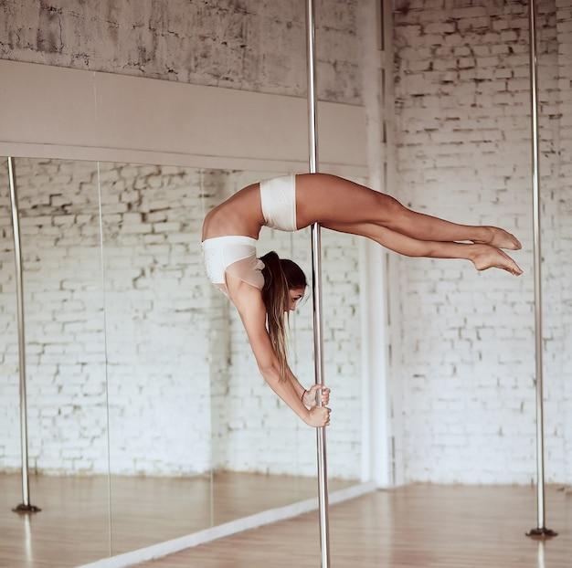 Impresionante joven delgada en ropa blanca realiza pole dance