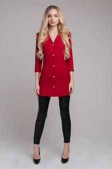 Impresionante modelo delgado con vestido rojo brillante y tacones negros.