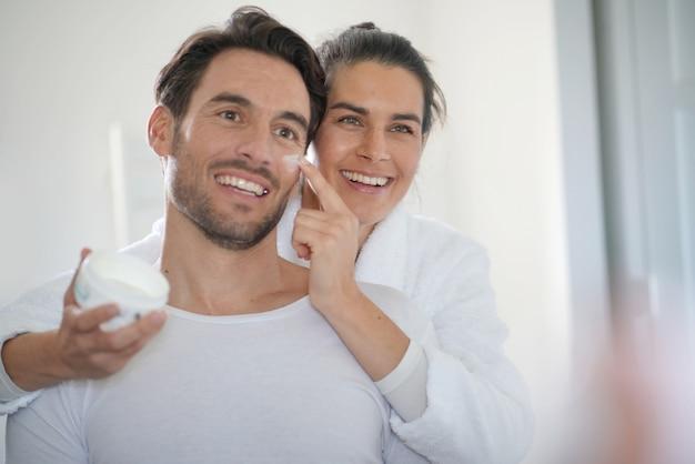 Impresionante morena aplicando crema facial en su apuesto compañero.