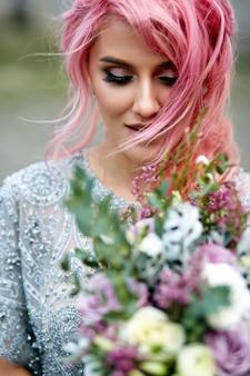 Impresionante mujer con cabello rosado se encuentra con gran ramo de boda