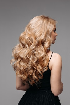 Impresionante mujer con cabello rubio ondulado perfecto.