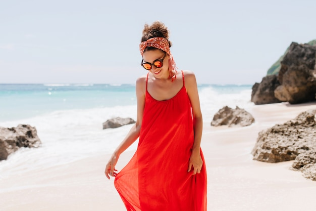 Impresionante mujer caucásica mirando hacia abajo mientras posa en la playa salvaje. disparo al aire libre de elegante dama bronceada de pie en la playa