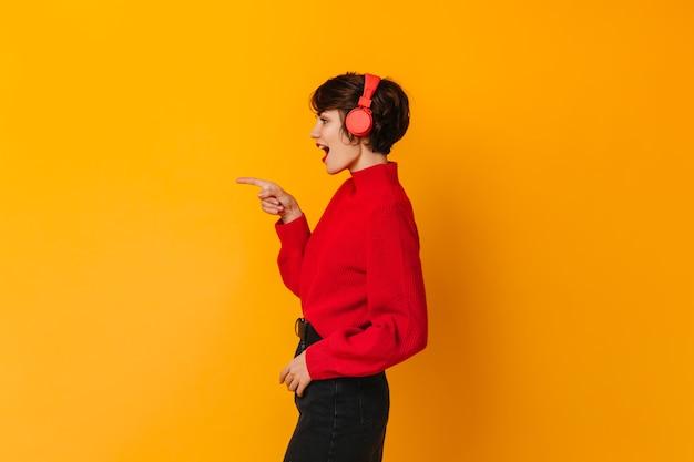 Impresionante mujer escuchando música y señalando con el dedo