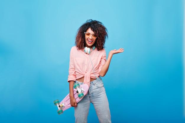 Impresionante mujer joven en jeans y camisa rosa con gafas de sol posando con una sonrisa sincera. linda chica africana con pelo rizado en auriculares sosteniendo patineta y riendo.