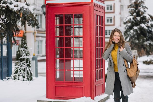 Impresionante mujer morena en cardigan amarillo de pie junto a la cabina de llamada británica en día de invierno. foto exterior de mujer adorable en abrigo de moda posando junto a la cabina telefónica
