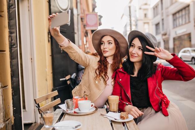 Impresionante mujer de pelo oscuro en chaqueta roja disfrutando de postre en la cafetería al aire libre, descansando con el mejor amigo