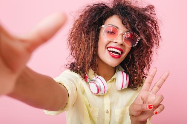 Impresionante mujer rizada con piel bronceada posando con el signo de la paz. complacida chica negra con camisa amarilla y grandes auriculares blancos.