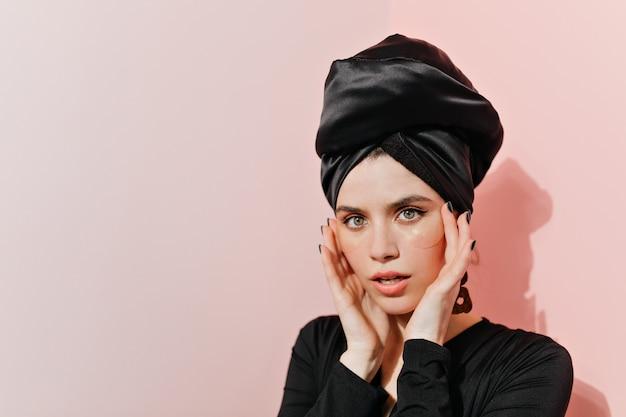 Impresionante mujer vestida de negro haciendo rutina de cuidado de la piel