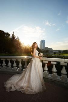 Impresionante novia en hermoso vestido de marfil posando al aire libre en la puesta del sol